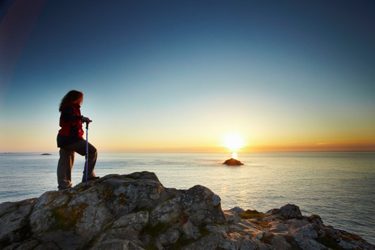 Hiker enjoying sunset on South West Coast path near Polzeath, Cornwall.